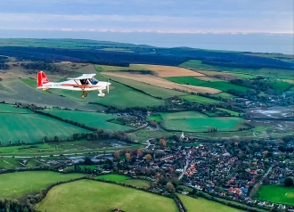 Formation flight, by Mikey McMahon. Mikey and Luke Christophides over the village of Alfriston in Sussex.